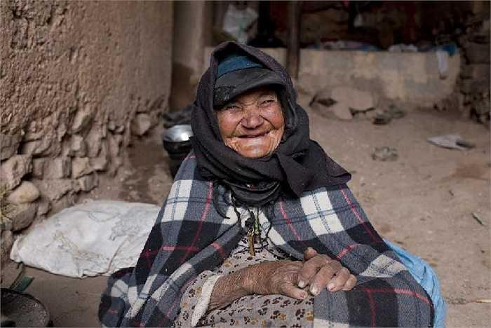 Nụ cười mãn nguyện của bà cụ khi hơi ấm của đống lửa xua tan cái giá lạnh của băng tuyết