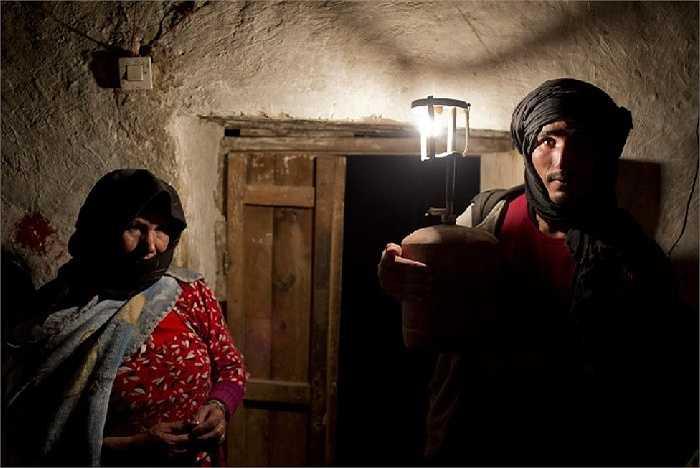 Ali và mẹ cùng chụp ảnh dưới ánh đèn dầu le lói trước cửa nhà
