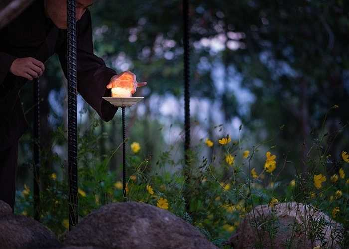 Khi trời sẩm tối, các nhà tu, phật tử có thể thắp nến trên một kệ ngay bên cạnh đó.