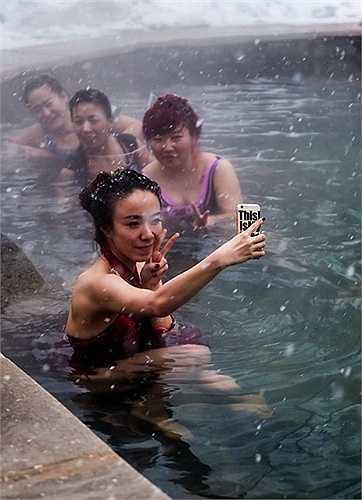 Nữ du khách thích thú tạo dáng trong suối nước nóng