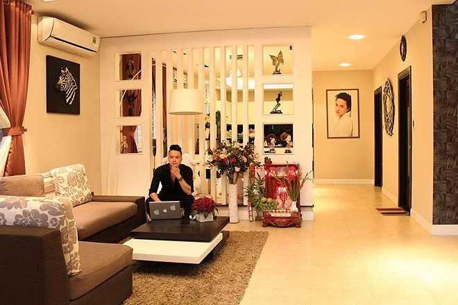 Phòng khách rộng với ánh sáng vàng, tạo sự ấm cúng cho căn nhà. Khác với mọi năm, Cao Thái Sơn thường đi diễn hoặc về Hà Nội đón Tết cùng gia đình, tuy nhiên, năm nay, anh ở lại Sài Gòn đón Tết đầu tiên trong căn nhà mới.