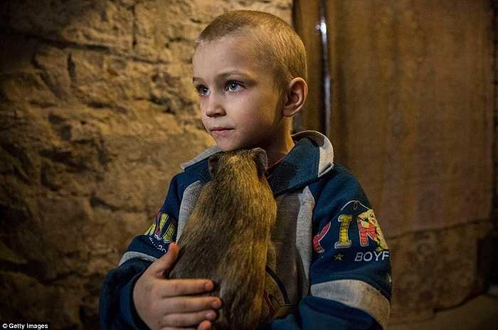 Pavel Makeev ôm thú cưng của em, được gọi là Masha đã chung sống với cậu bé kể từ ngày chuyển xuống hầm trú ẩn