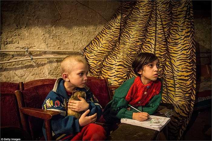 Cậu bé và chị gái sống bên trong hầm trú ẩn để tránh đạn pháo