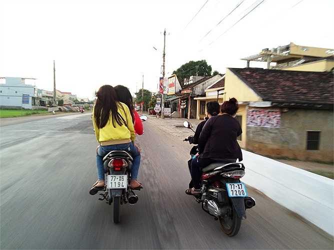 Thiếu nữ đầu trần chở nhau chạy xe trên QL1A thuộc huyện Tuy Phước. Ảnh: Hạnh Phương