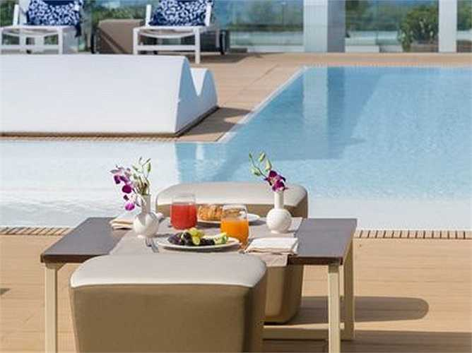 Ảnh cận cảnh cho thấy một bữa sáng thịnh soạn phục vụ khách ngay tận bể bơi của khách sạn Le Dune Suite ở Puglia, Italia.