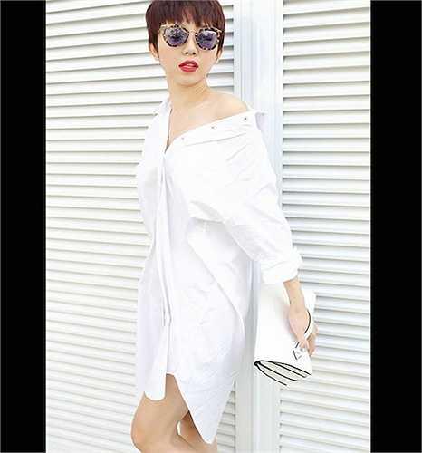 Tóc Tiên - nữ ca sỹ kiêm tín đồ thời trang cá tính nhất nhì Việt Nam hiện nay sành điệu với sơ mi trắng kéo lệch vài và clutch (túi nhỏ cầm tay) cùng tông trắng.