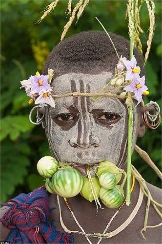 Cô gái Surma ở thung lũng Omo, Etiopia có tục vẽ mặt và đội mũ dược làm từ hoa và trái cây