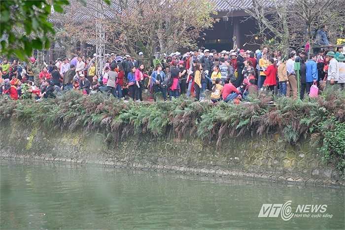 Mới khoảng 9h sáng, hàng nghìn người đã xếp hàng kín sân chờ lối vào soát vé. Lực lượng kiểm soát mỏng nên du khách tràn ra mép bờ kênh, đứng chênh vênh