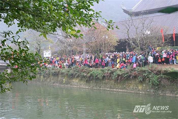 Những người đi tham quan danh thắng Tràng An vào những ngày chủ nhật đều phải chờ đợi mấy tiếng đồng hồ trong cảnh 'cheo leo' như thế này