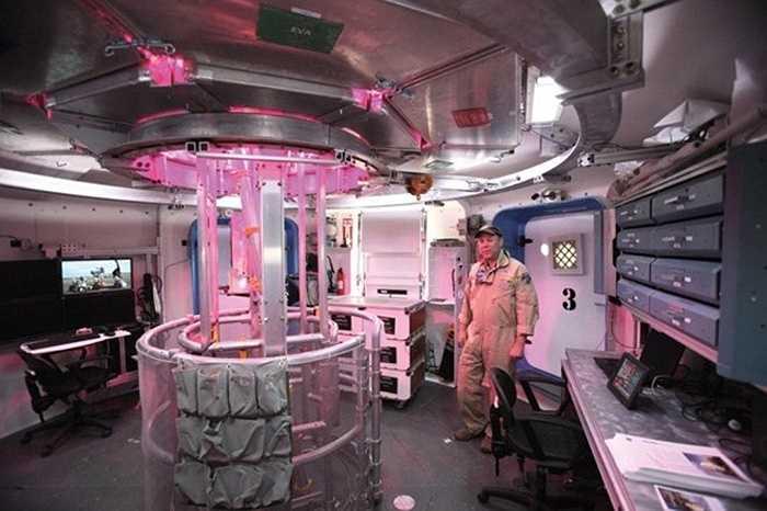 Một phi hành gia bên trong một trạm nghiên cứu HDU. Ở giữa phòng là một hệ thống trồng cây, sử dụng ánh sáng đỏ xanh để kích thích tăng trưởng.