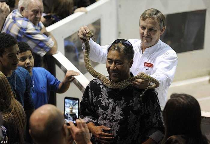 Một người dân quàng một con rắn quanh cổ mình