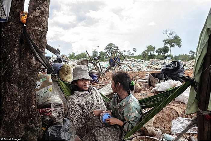 Hael Kemra (trái), 15 tuổi và Suy Sokhon (bên phải), 16 tuổi. Hai chị em đang nghỉ ngơi trên võng cạnh bãi rác để chờ xe tải rác tiếp theo đến