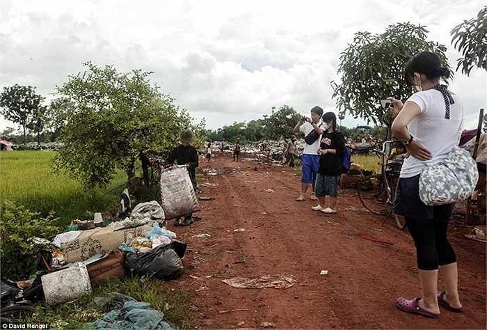 Một nhóm khách du lịch đang chụp hình Sueun Chany, 12 tuổi, đang phân loại rác trên đường