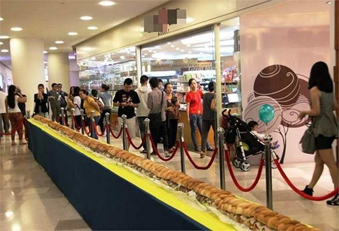 Gần 500 người đứng xếp hàng ở trung tâm thương mại lớn ở quận 1, TP HCM để thưởng thức ổ bánh mì khổng lồ dài 18 m, nhân bánh gồm thịt bò, heo, gà và xà-lách.