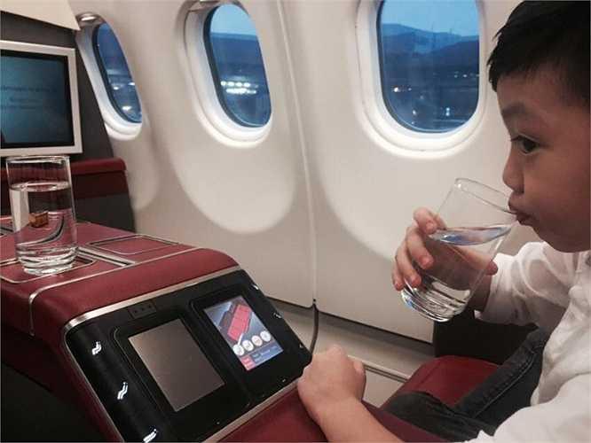 Cậu nhóc thích thú khám phá chỗ ngồi của mình trên máy bay.