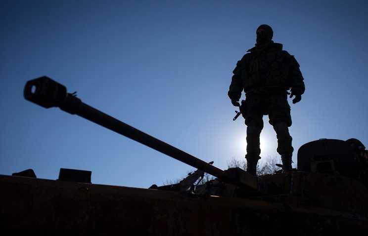 Binh sĩ đứng trên chiếc xe tăng bị hư hại ở Smeloye, Ukraine