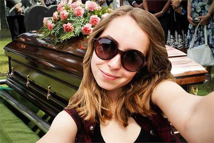 Một cô gái xinh đẹp chụp hình bên chiếc quan tài người chết