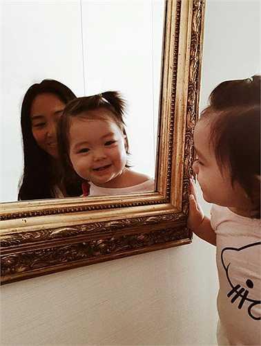 Bé Sol cười tươi, khoe hai chiếc răng sữa mới nhú khi soi gương cùng mẹ. (Nguồn: Ngôi sao)