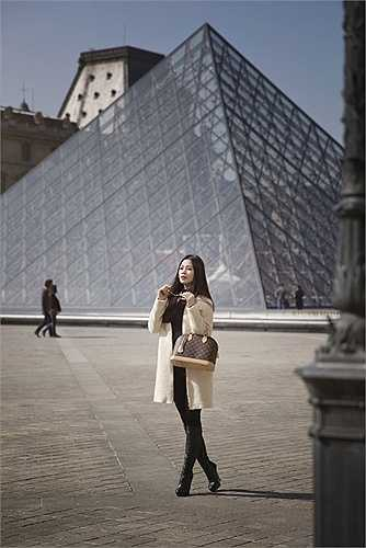 Diễm Trang tự làm stylist cho chính mình với áo khoác dài phối cùng giày bốt, mũ, kính, vòng cổ ngọc trai và túi hiệu Louis Vuitton.