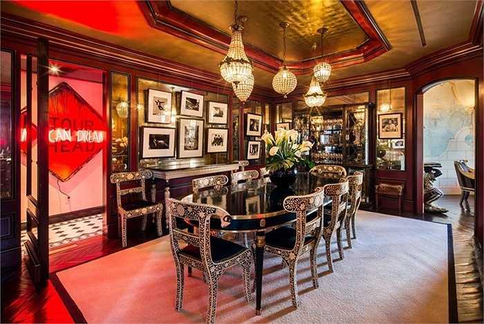 Phòng ăn và quầy bar được trang trí với đèn neon, đèn chùm và tường bằng vàng.