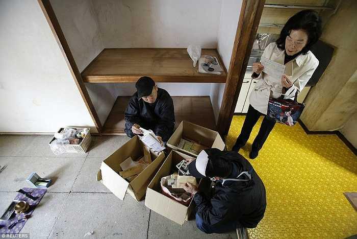 Chủ căn hộ và các nhân viên dọn rác kiểm tra lại đồ đạc của cụ ông.