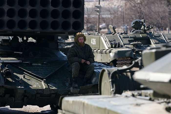 Binh sĩ ngồi cạnh xe thiết giáp gắn giàn phóng tên lửa