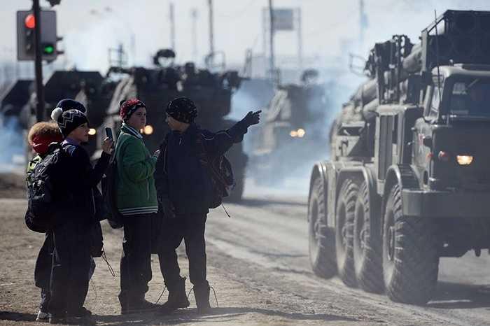 Các cậu bé chụp ảnh những thiết bị quân sự trên đường phố