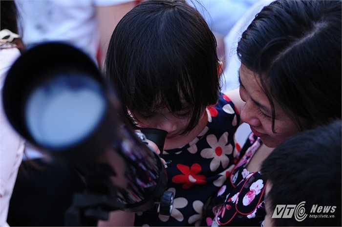 Bé gái được mẹ cho ngắm kính thiên văn