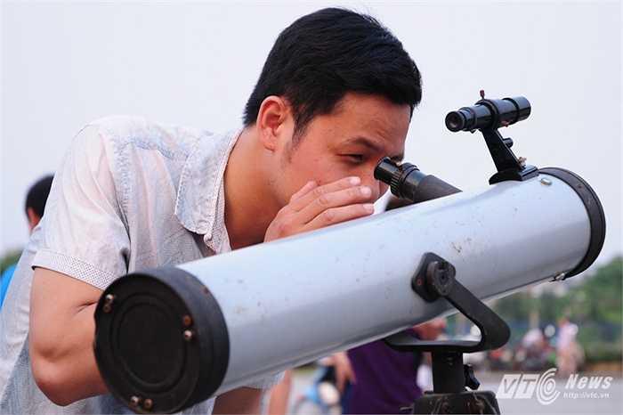 Một thanh niên thử nhìn vào kính thiên văn tự chế