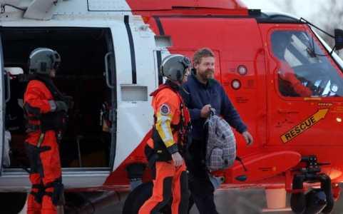 Anh Louis Jordan (phải) bước ra khỏi trực thăng cứu thương