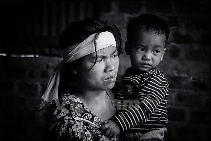 Đã 4 ngày kể từ thảm họa tại Formosa nhưng chị Thương (xã Lâm Trạch, Bố Trạch, Quảng Bình) vẫn không thể tin được vào những gì đã xảy ra. Mắt đỏ hằn, chị ôm chặt đứa con út vào lòng, đờ đẫn hướng ra đoạn đường đang chạy hút vào cánh rừng xa mà khóc. Chồng chị, anh Nguyễn Văn Lịch đã vĩnh viễn không trở về. (Ảnh: Minh Sơn/Vietnam+)