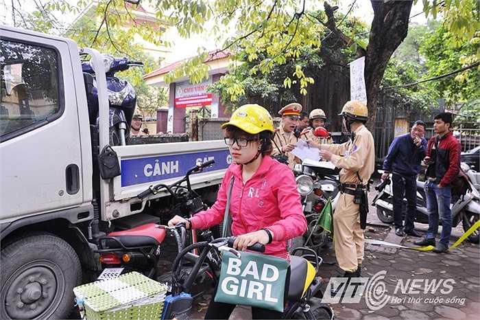 Mũ bảo hiểm có ở xe nhưng sau khi bị CSGT xử phạt, nữ sinh này mới chịu đội. (Ảnh: Minh Chiến)