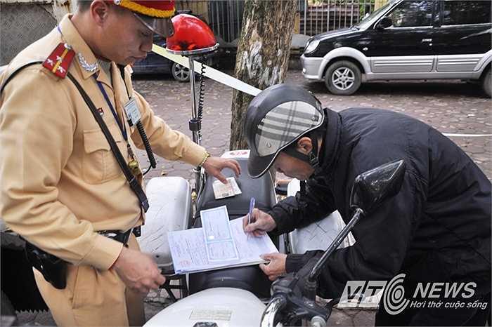 Phụ huynh NGuyễn Đức Thuận ký vào biển bản nộp phạt hành vi chở người ngồi sau xe máy không đội mũ bảo hiểm.