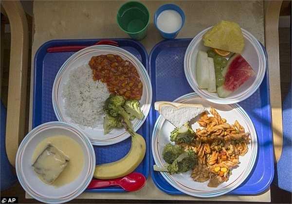 Còn đây là hai phần ăn tại một trường tiểu học ở London, Anh. Bên phải bao gồm mì ống với bông cải xanh cùng một lát bánh mì và trái cây. Ở bên trái là cơm, rau và súp lơ xanh, bánh bông lan với mãng cầu và chuối để tráng miệng.