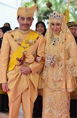 Cô dâu cầm hoa cưới pha lê, trên người đeo bộ trang sức gồm vương miện, vòng cổ và nhẫn làm bằng ngọc lục bảo kích cỡ lớn