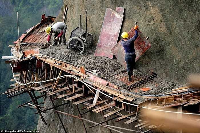 Những công nhân thi công trên con đường nằm giữa vách đá ở tỉnh Hồ Nam, Trung Quốc