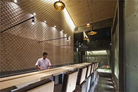 Bức tường vảy cá ấn tượng đằng sau lưng đầu bếp của nhà hàng.