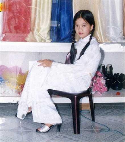 Ngọc Trinh mặc áo dài, thắt bím tóc trông rất duyên dáng. Ở miền Tây, học sinh cấp 2 thường mặc áo dài đi học.