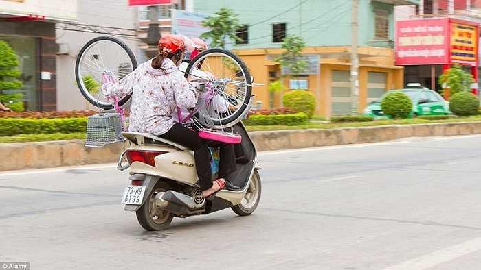 Người phụ nữ ôm xe đạp ngồi sau xe máy trên đường phố ở Việt Nam.