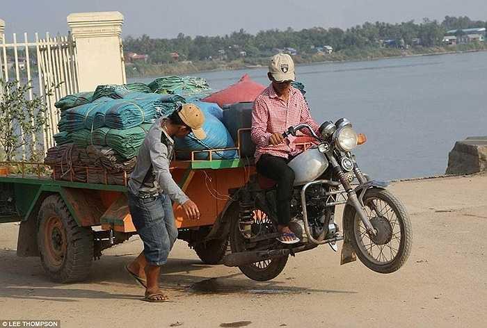 Người đàn ông kéo xe moóc được nối với xe máy tại một bến phà qua sông Cửu Long ở Việt Nam.