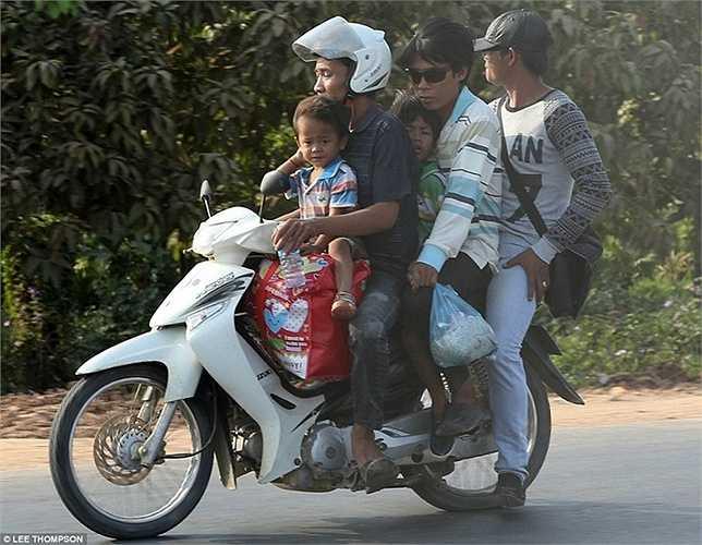 Một gia đình 5 người ngồi trên một chiếc xe máy tại Hà Nội.