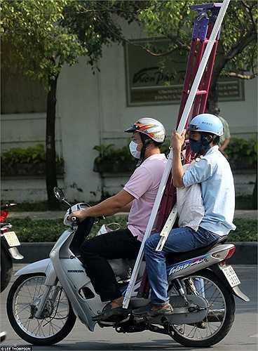 Người đàn ông ngồi sau xe máy ôm theo thang và vật liệu xây dựng trên đường phố ở Hà Nội.