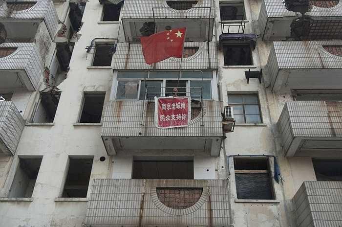 Xu Aiguo, chủ một nhà 'đinh' vẫy quốc kỳ Trung Quốc trên ban công ở Nam Kinh Giang Tô, Trung Quốc vào năm 2010. Tấm băng rôn màu đỏ ghi chữ: 'Người dân từ các huyện phía nam cũ của Nam Kinh sẽ hỗ trợ cho bạn'