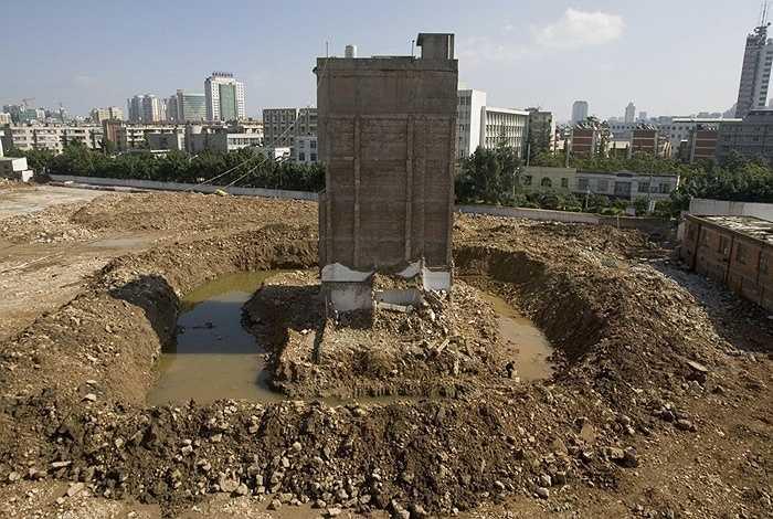 Ngôi nhà 'đinh' đã bị phá một phần nằm giữa một hố nước tại công trường dự án ở Côn Minh, Vân Nam, Trung Quốc năm 2010.
