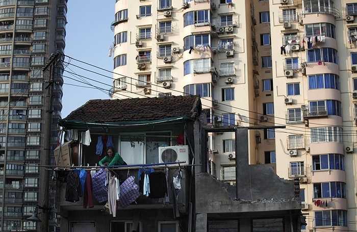 Một phụ nữ đứng trên ban công căn nhà lẽ ra đã được giải tỏa để nhường chỗ cho những tòa nhà chung cư cao tầng ở Thượng Hải, cuối năm 2010.