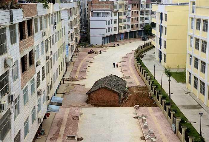 Một ngôi nhà nằm ngay giữa đường đang xây ở một khu tự trị tại Nam Ninh, Quảng Tây, Trung Quốc. Nó như kết quả của việc chủ nhân ngôi nhà đã không đạt được thỏa thuận cuối cùng với chính quyền về tiền bồi thường giải tỏa.
