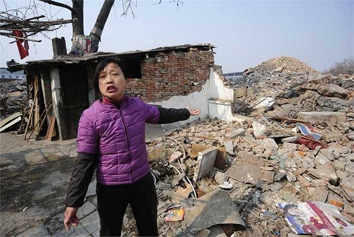 Cô Cao Mingyun và ngôi nhà của mình ở Hợp Phì, An Huy, Trung Quốc vào năm 2010. Gia đình cô từ chối chuyển đi do không nhất trí với mức bồi thường của chủ dự án thương mại đưa ra.