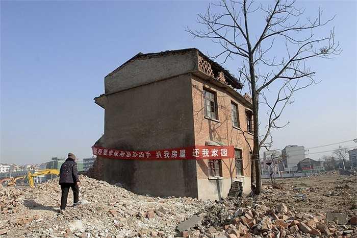 Một nhà 'đinh' nằm trong khu dự án chung cư ở Hợp Phì, An Huy, Trung Quốc năm 2008. Ngôi nhà này treo một tấm băng-rôn đỏ rực ghi chữ: 'Đề nghị chính quyền trừng trị chủ đầu tư phá nhà của tôi. Trả lại nhà cho tôi'.
