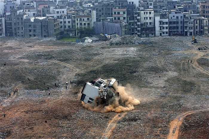 Đây là hình ảnh người ra 'nhổ' một ngôi nhà 'đinh' ở một công trường tại Quảng Châu, Quảng Đông, Trung Quốc vào năm 2008. Chủ căn nhà này đã kiện chủ đầu tư để đòi thêm tiền bồi thường, tuy nhiên cuối cùng đã bị thua kiện.