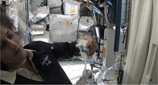 Một phi hành gia chuyển nước từ vòi vào bàn chải để đánh răng.